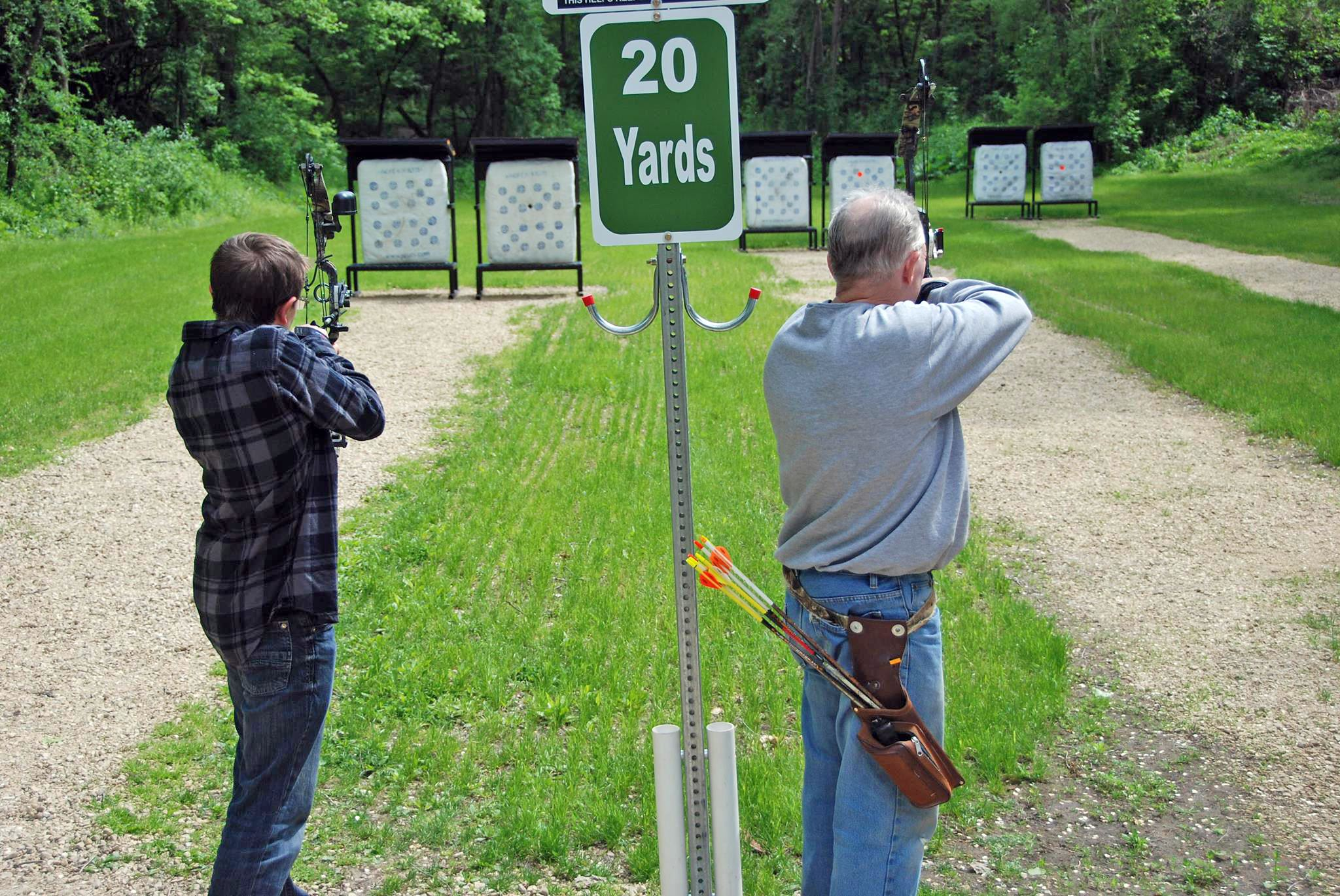 South St. Paul Archery Range, two people aiming at targets 20 foot away.